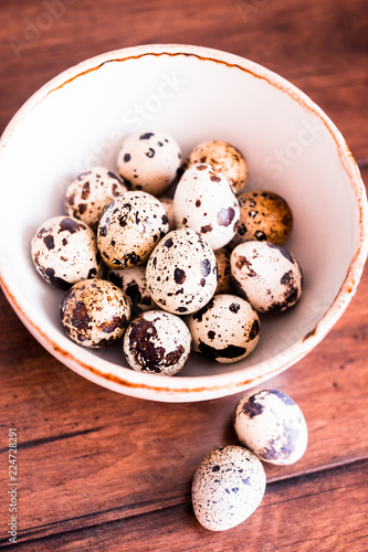 Quail eggs on a wooden vintage table, selective focus. Healthy and organic food option. Easter food. Easter symbol.