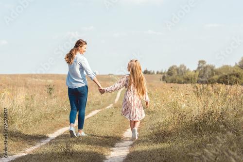 Vászonkép rear view of mother and daughter holding hands and walking together in field