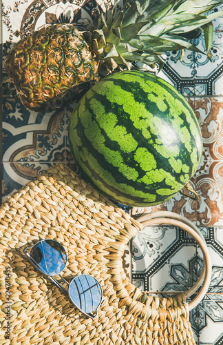 Summer lifestyle background. Flat-lay of summer fruit pineapple and watermelon, straw bag and sunglasses over colorful moroccan tile floor, top view, vertical