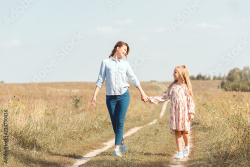 Fotografie, Tablou  happy mother and daughter holding hands and walking together in field