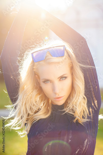 Poster Natuur Blonde woman with a beautiful beaming backlit by the warm glow of the sun