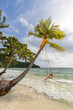 Young woman on a swing on exotic tropical sandy Bai Sao beach in the sea under a palm tree