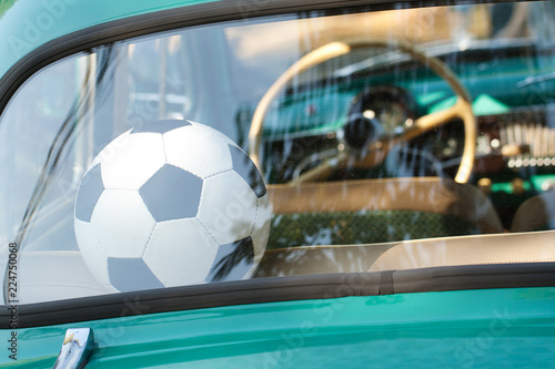 soccer ball lies in an old car in the back seat in anticipation of a game or training session - 224750068