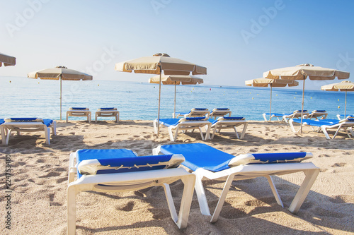 Staande foto Strand Loungers on a tropical beach. Sun beds and umbrellas on a sandy beach. Summer vacation at the sea