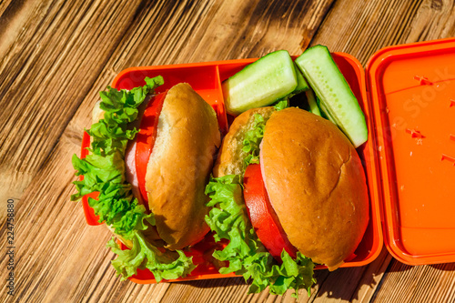 Foto op Aluminium Assortiment Hamburgers with lettuce in lunchbox on wooden table. Top view