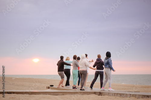 Fototapeta group of people doing exercises at sunrise meet the sun, doing yoga, a healthy lifestyle obraz