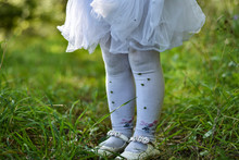 The Legs Of A Little Girl In A White Dress And Pantyhose On The Grass In The Forest Are Stained In The Ground, Grass And Thorns, Old Torn Shoes
