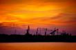 Leinwandbild Motiv View on seaport with cranes at sunset. Evening panorama of the cargo port