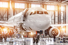 Passenger Commercial Airplane On Maintenance Of Engine Turbo Jet And Fuselage Repair In Airport Hangar. Aircraft With Open Hood On The Nose And Engines, As Well As The Luggage Compartment.