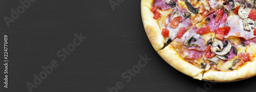 Freshly baked pizza on black background, close-up. Flat lay, overhead, from above. Copy space.