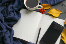 A Book With A Cup Of Tea And A Mobile Phone Surrounded By Autumn Leaves On A Gray Background, White Pages For Writing, Copy Space.