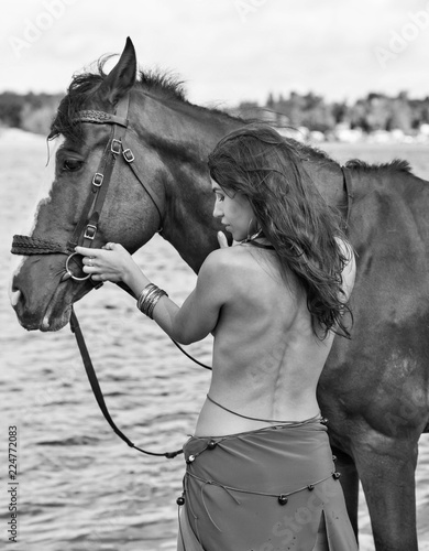 horse and young beautiful naked Amazon woman on river shore