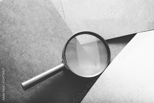 magnifier on grey layered paper background. searching seeking looking recruiting and headhunting concept.