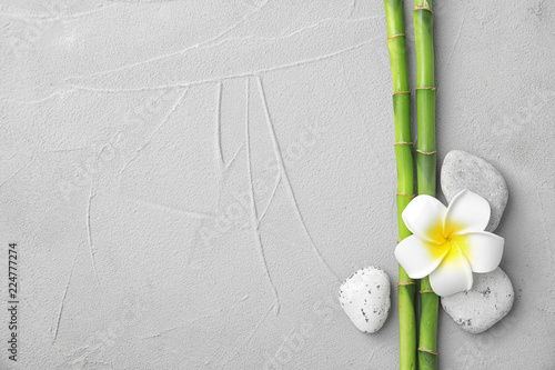 Composition with bamboo branches, stones and plumeria on light background, top view. Space for text