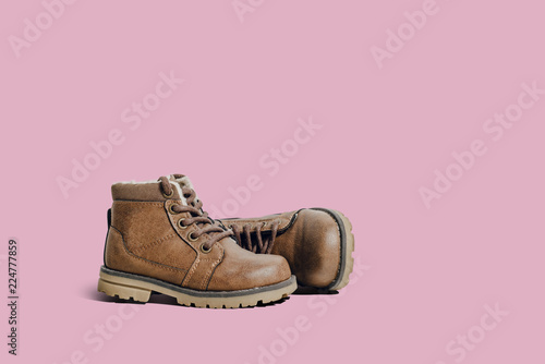 A pair of leather, children's shoes on a pink pastel background. The concept of upcoming cold, selling shoes. A warm, comfortable shoe for children with fur.