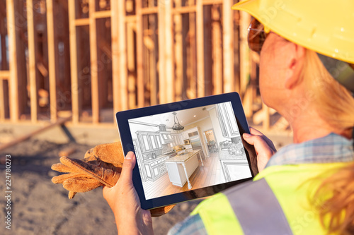 Fotografie, Obraz  Female Construction Worker Reviewing Kitchen Illustration on Computer Pad at Con