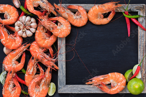 Perfect cooked prawns shrimps with herbs, spices and text space chalk board top view flat lay