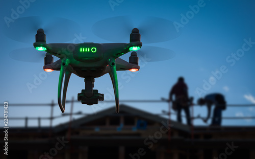Papiers peints Akt Silhouette of Unmanned Aircraft System (UAV) Quadcopter Drone In The Air at Construction Site