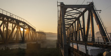 A Railway Bridge In The Morning Fog Or Smoke Through Which The Rays Of The Sun Shine