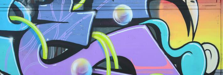 Fragment rysunków graffiti. Stara ściana ozdobiona plamami farby w stylu kultury ulicznej. Kolorowa tło tekstura w zimnych brzmieniach