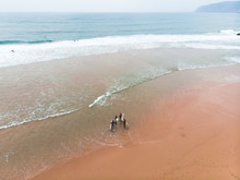View Of Praia Do Guincho, Guincho Beach, A Popular Atlantic Ocean Beach On Portugal's Estoril Coast, Municipality Of Cascais, With Surfers Surfing On The Waves, Shot From Drone