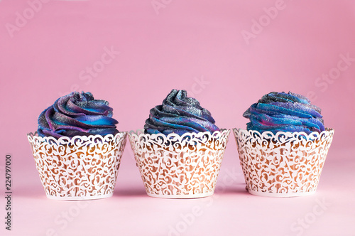 Galaxy cupcakes on pink background with copyspace