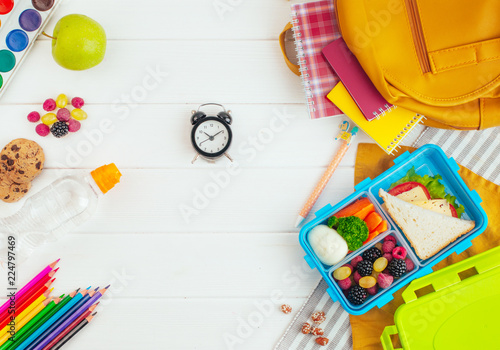 In de dag Assortiment Lunch box on white wooden background near school accessories and backpack