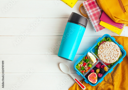 Lunch box on white wooden background near thermo mug and school accessories