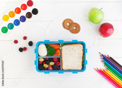 In de dag Assortiment Open lunch box with sandwich, vegetables, egg, fresh berries on the white wooden background. Top view, flat lay.