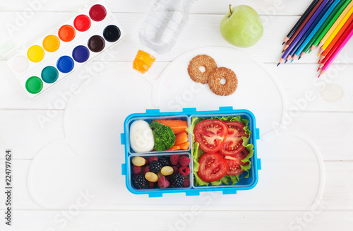 In de dag Assortiment Lunch box with sandwich, vegetables, berries on white wooden background with school accessories