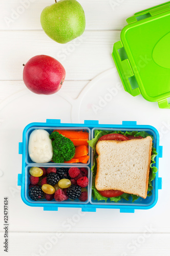 In de dag Assortiment Open lunch box with sandwich, vegetables, egg, fresh berries on the white wooden background with copy space. Top view, flat lay.