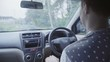 Nice looking mature caucasian short haired man dressed in t-shirt is dance moving on his seat and driving right hand drive car in eastern tropical rural road on cloudy summer day.