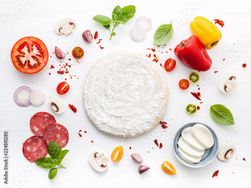 The ingredients for homemade pizza on white wooden background..