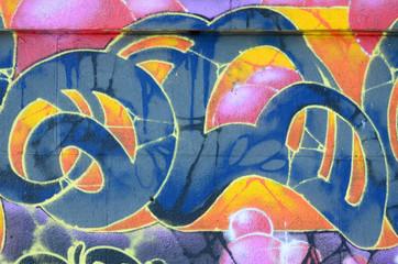 Fragment rysunków graffiti. Stara ściana ozdobiona plamami farby w stylu kultury ulicznej. Kolorowe tło tekstury w ciepłych kolorach