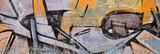 Fragment rysunków graffiti. Stara ściana ozdobiona plamami farby w stylu kultury street art. Kolorowe tło tekstury w ciepłych kolorach