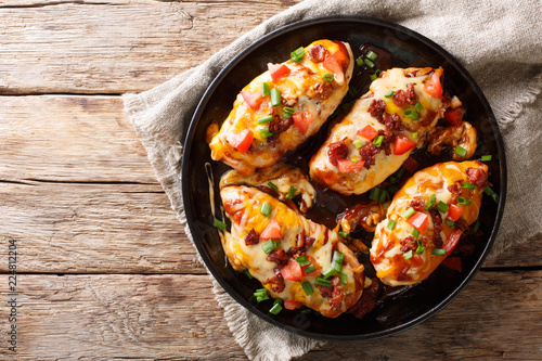 Chicken breast baked with monterey cheese and cheddar, bacon, tomatoes and barbecue sauce close-up. Horizontal top view