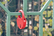 Closed Red Padlock In The Form Of A Heart On The Fence, A Symbol Of Strong And Unbreakable Family Relations, Closed By The Bride And Groom On The Wedding Day