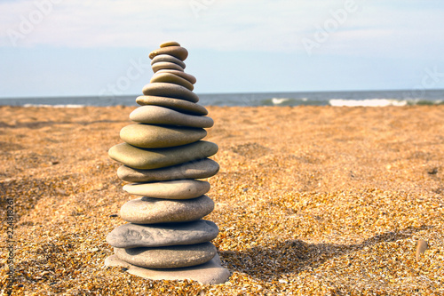 Stones pyramid on sand symbolizing zen, harmony, balance. Sea in the background