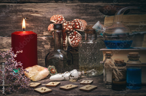 Fotografie, Obraz  Magic potion, runes for divination and stack of old books on the magician table