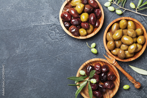 Assortment from marinated olives in wooden bowls top view.