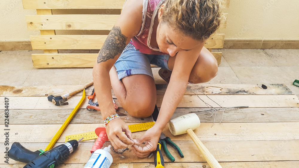 Fototapety, obrazy: woman working outdoor with hardware stuffs building furniture or something for home with recycled pallets pine wood. do it yourself hobby concept