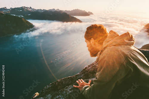 Fototapeta Man on the edge cliff above sea gaze into abyss lying down traveling in mountains adventure lifestyle extreme vacations obraz