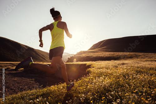 Young fitness woman trail runner running on sunset grassland