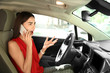 Displeased young woman talking by mobile phone on driver's seat of car