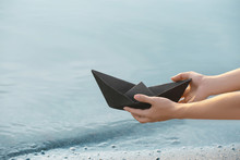 Woman Holding Origami Boat Near River