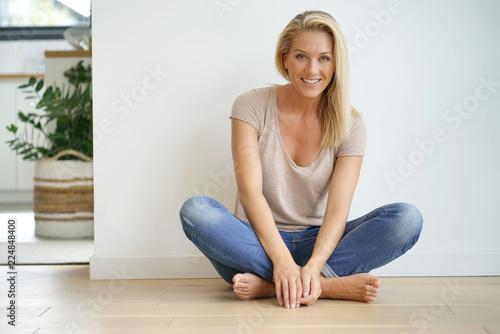 Carta da parati Beautiful blond woman sitting on floor against white wall