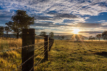 Country Timber Post Fence Line Leading To Sunrise And Cloudy Sky