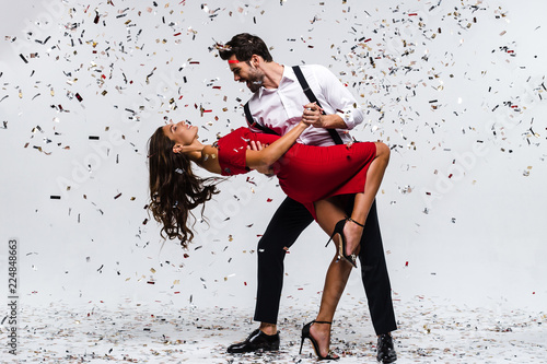 rumba-time-full-length-of-young-beautiful-couple-dancing-while-standing-against-white-background-with-confetti
