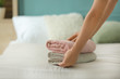 Woman putting clean folded towels on bed