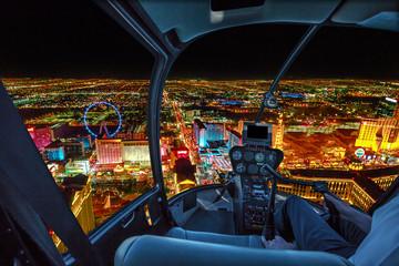 Wnętrze śmigłowca na budynkach w Las Vegas i wieżowcach śródmieścia z oświetlonymi hotelami kasynowymi w nocy. Sceniczny lot nad Vegas panoramą nocą w Nevada Stany Zjednoczone Ameryka.